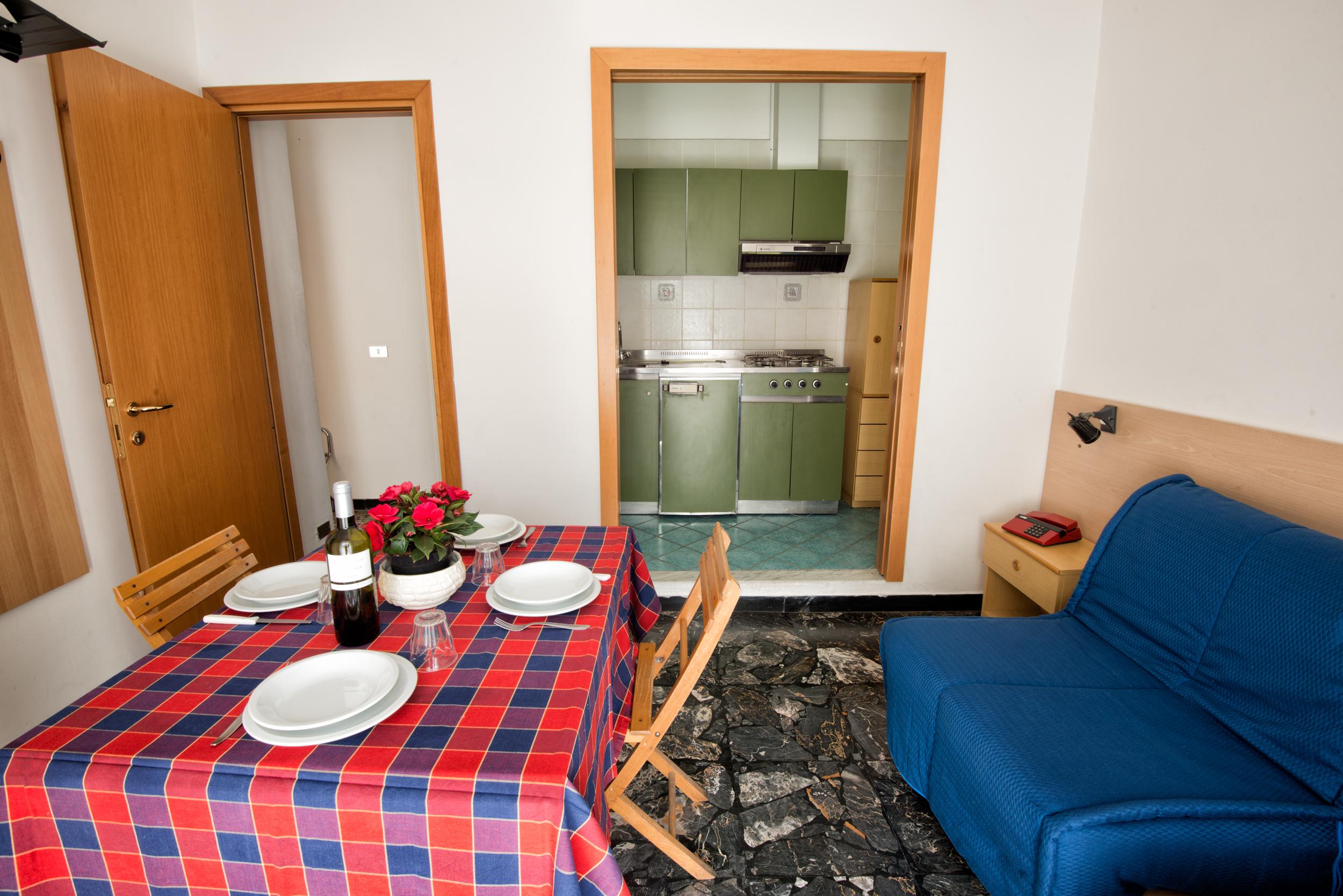 vano soggiorno con due posti letto e angolo cottura